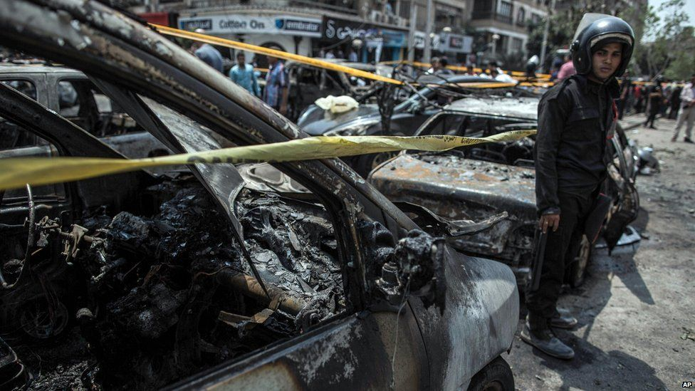 Egyptian policeman stands beside a car destroyed in a bombing that killed Prosecutor General Hisham Barakat (29 June 2015)