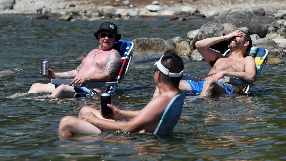 Посетители пляжа сидят в воде у озера Алуэтт, чтобы остыть в палящую погоду из-за волны тепла в Мейпл-Ридж, Британская Колумбия.