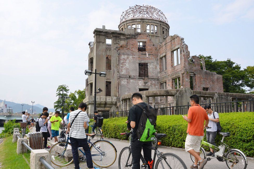 People play Pokemon Go near the Atomic Bomb Dome at Hiroshima Peace Memorial Park in Hiroshima on 26 July 2016.