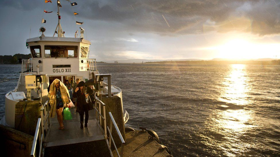 This file photo taken on August 24, 2012 shows tourists coming back from the Hovedoya island in the Oslo fjord during a rain shower as they disembark from a ferry in Oslo at sunset.
