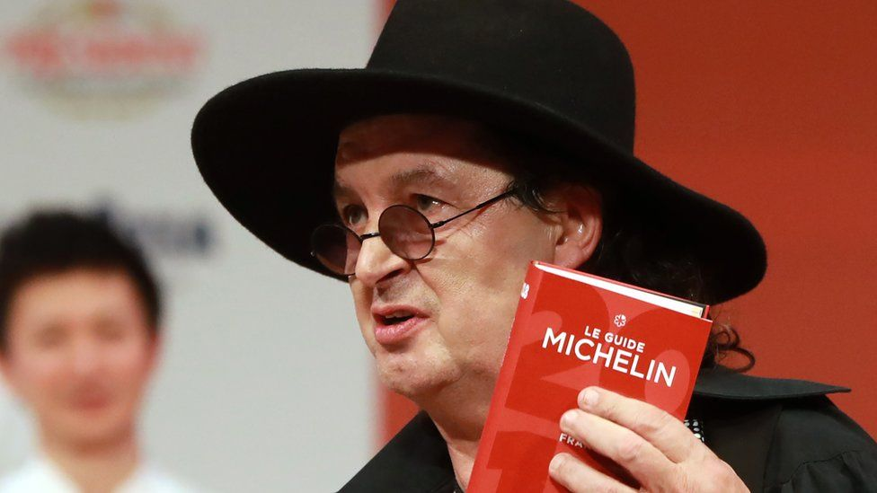 French chef Marc Veyrat, holds a Michelin guide after being awarded the maximum three Michelin stars at La Seine Musicale in Boulogne-Billancourt near Paris, 5 February 2018