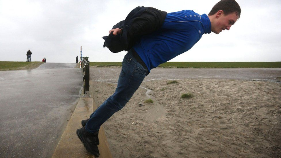 A man stands on the edge of a seawall in Harlingen in the Netherlands, 9 February 2020