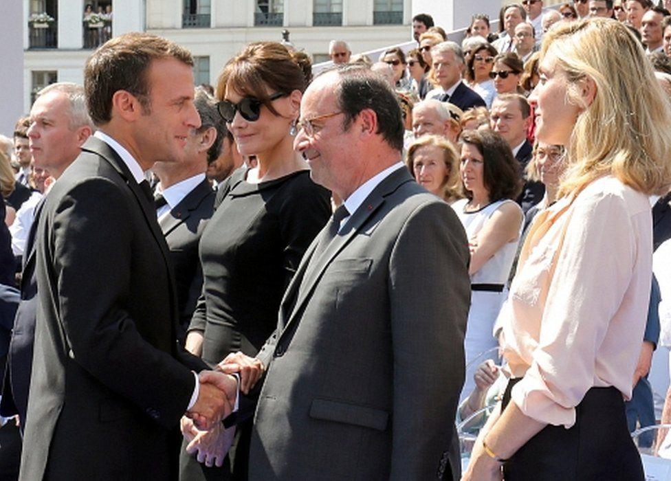 French President Emmanuel Macron shaking hands with predecessor Francois Hollande