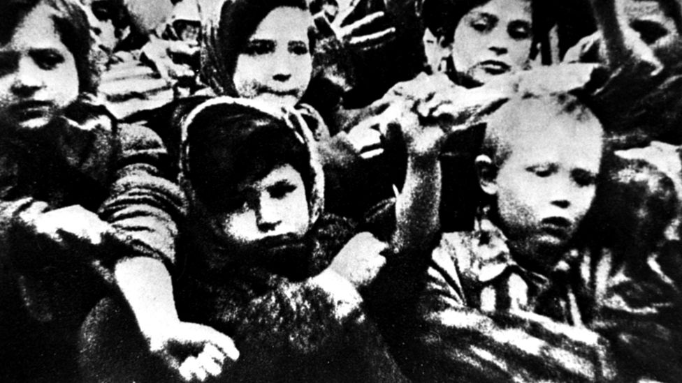Дети в Освенциме показывают татуировки на руках