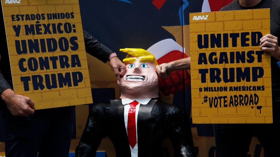 A couple of men hit a pinata representing U.S. Republican presidential candidate Donald Trump leaning against a symbolic wall, at the Independence Angel monument in Mexico City, Sunday, Sept. 25, 2016