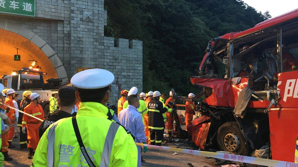 Police and firefighters work near the wreckage of a coach in Shaanxi province, 11 August