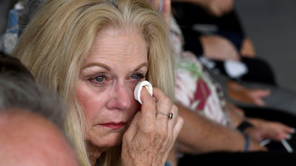 A woman cries as caskets are handed over in Honolulu, Hawaii
