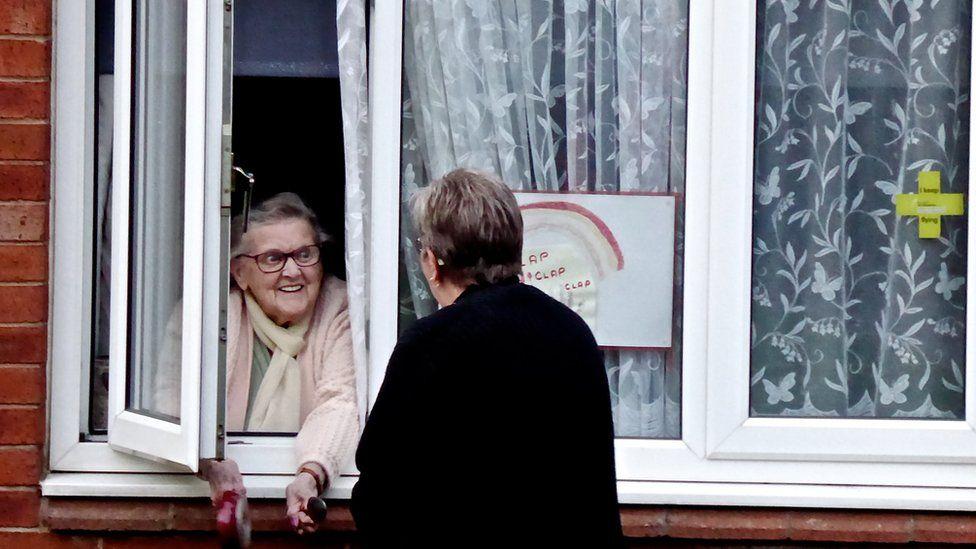 Two women talking at a window