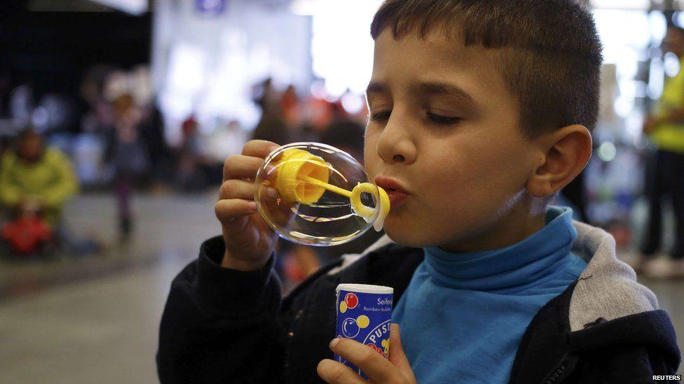 A migrant boy blows bubbles in Austria