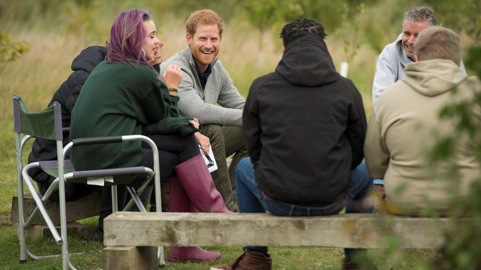 Harry chats with youngsters around the bonfire
