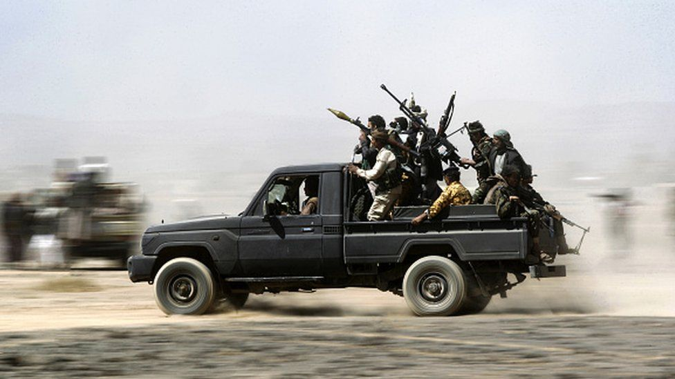 Armed Yemeni tribesmen loyal to the Houthi rebels sit in the back of an armed vehicle