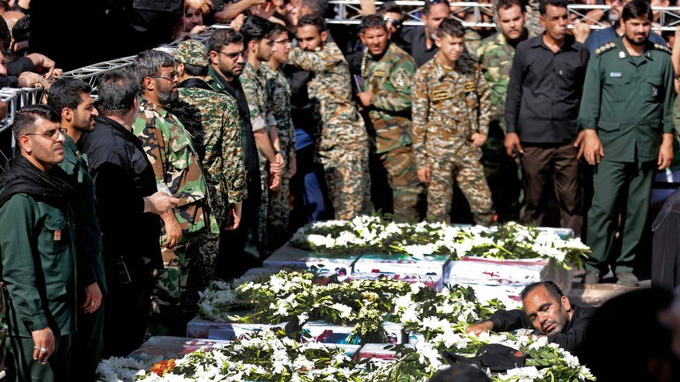Iranian military personnel mourn over the bodies of people killed in the attack on a military parade in Ahvaz (24 September 2018)