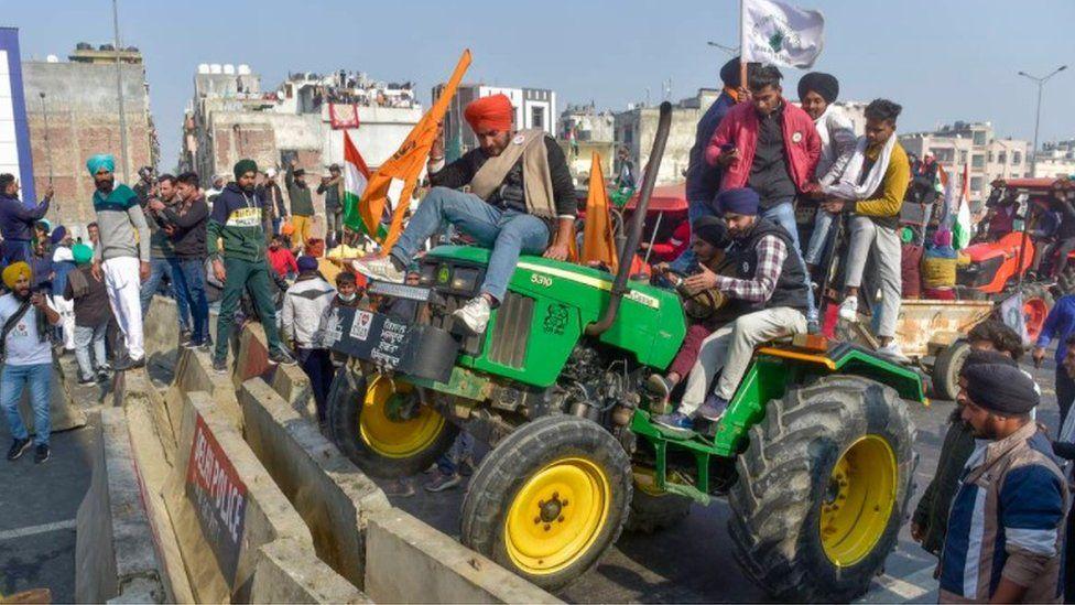 Farmers run a tractor over a barricade at the Delhi- Ghazipur border.