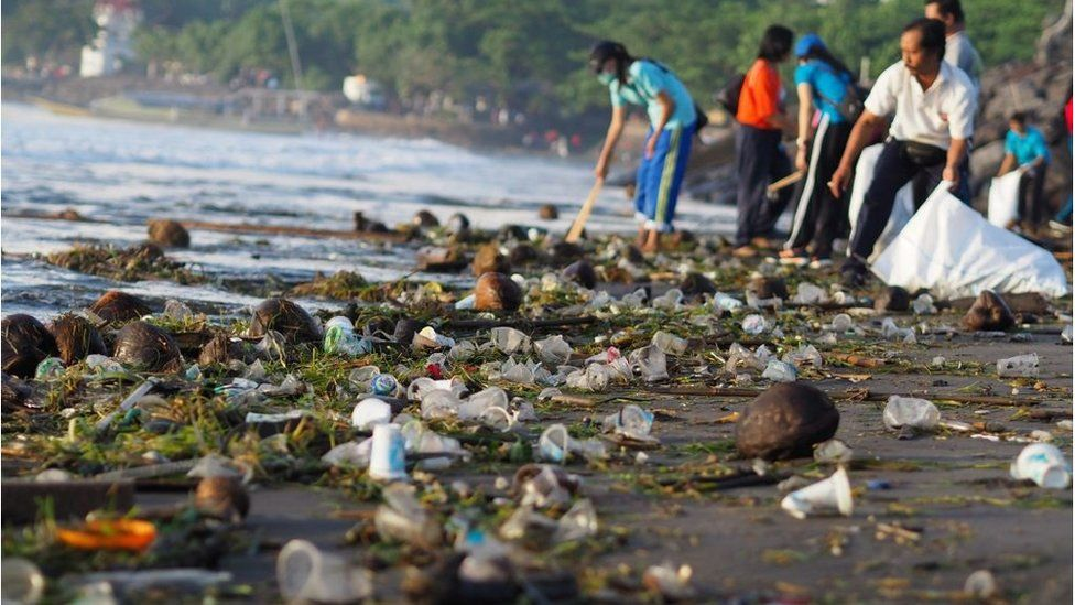 People and children work together cleaning up Sanur Beach from plastics and woods waste in Bali on April 13, 2018