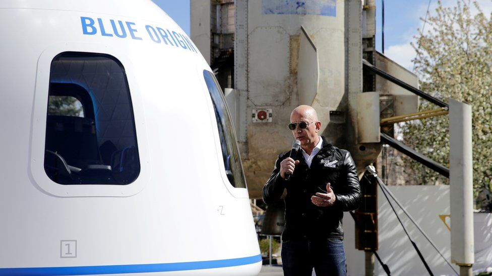 Jeff Bezos addresses the media next to the New Shepard launch vehicle