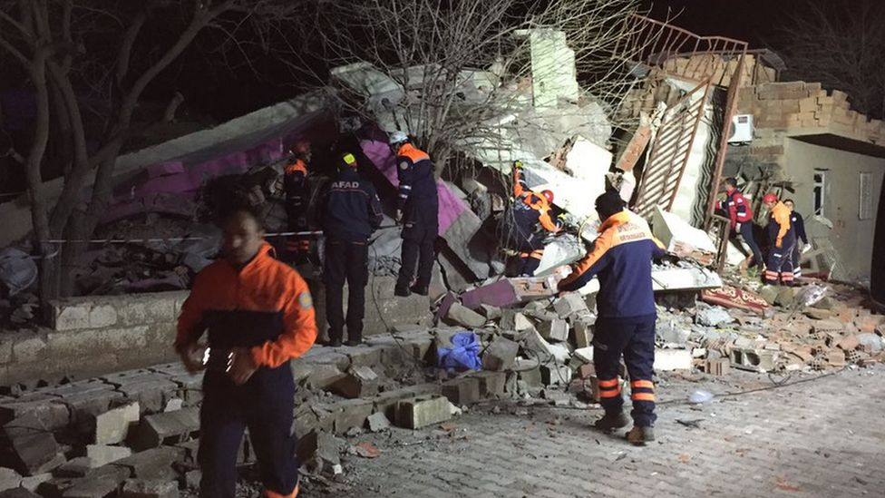 Rescuers at the destroyed police HQ in Cinar