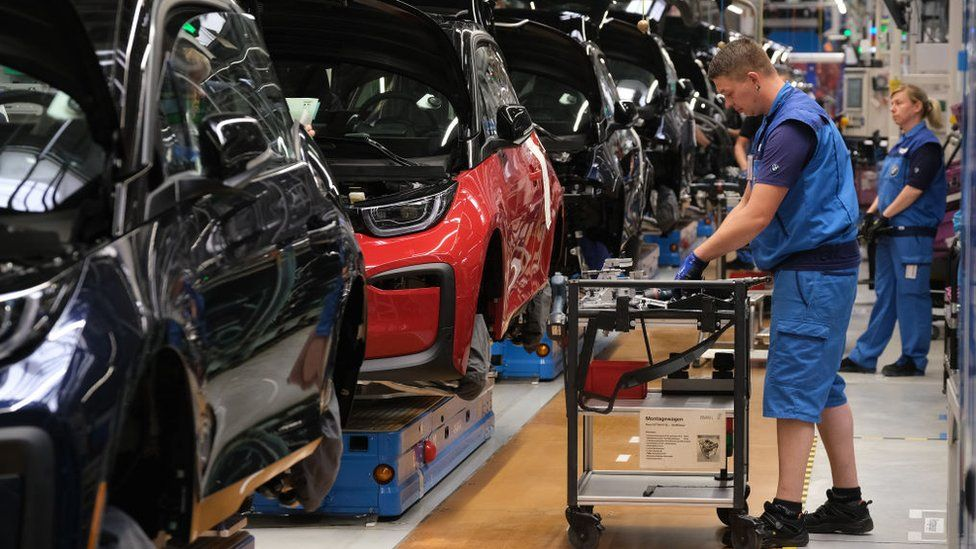 BMW workers assemble electric cars at an assembly line in Leipzig