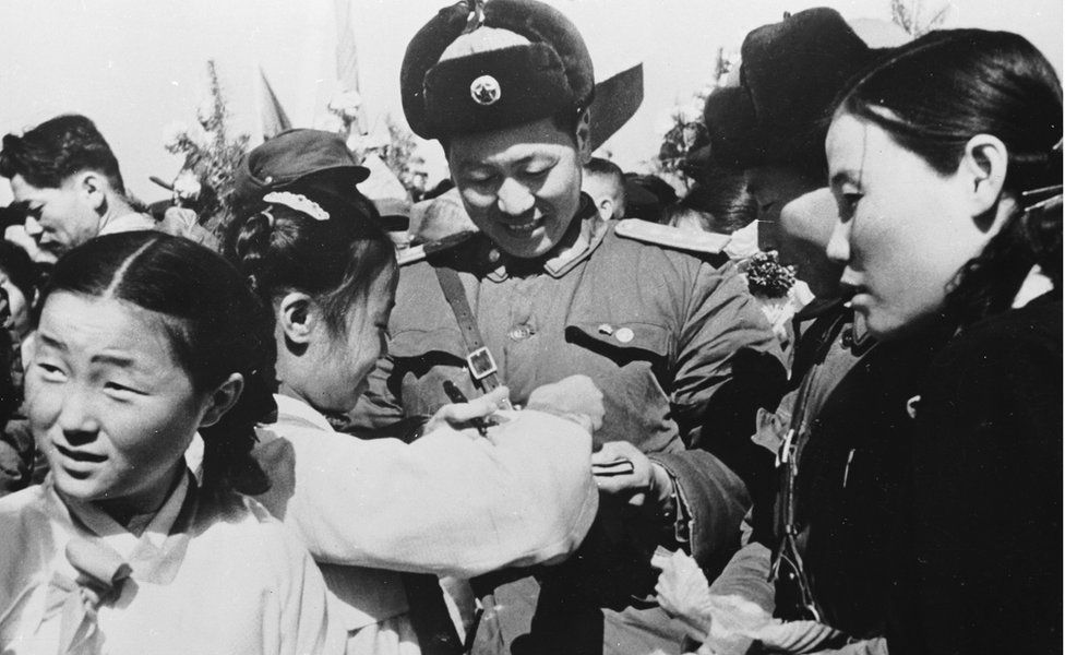 Korean girls present a member of the Chinese People's Volunteer Army with a bouquet of flowers prior to the mass withdrawal of Chinese troops from North Korea in 1958