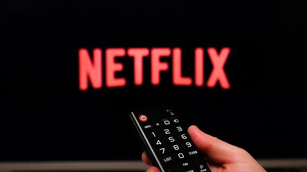 Netflix logo on a TV with hand holding remote
