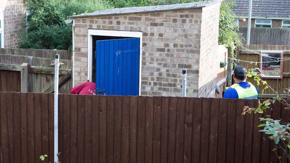 Officers inspect outhouse