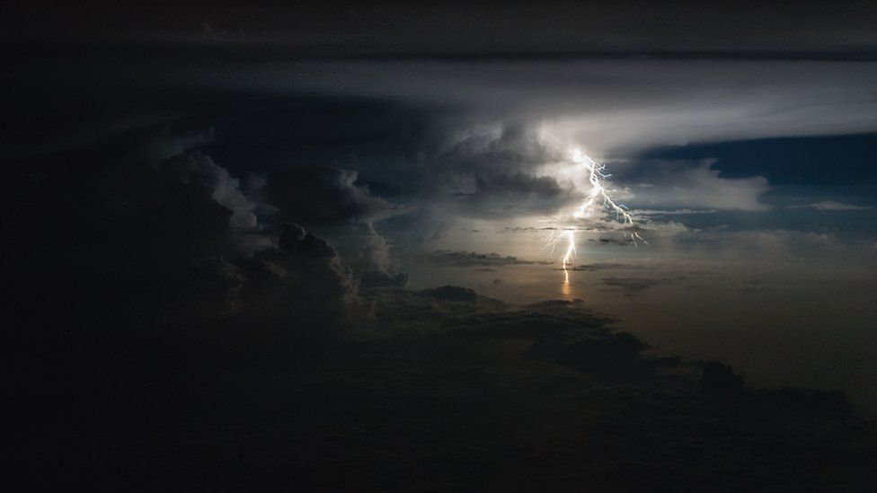 Lightning illuminates the sky in the distance in a frame of dark clouds