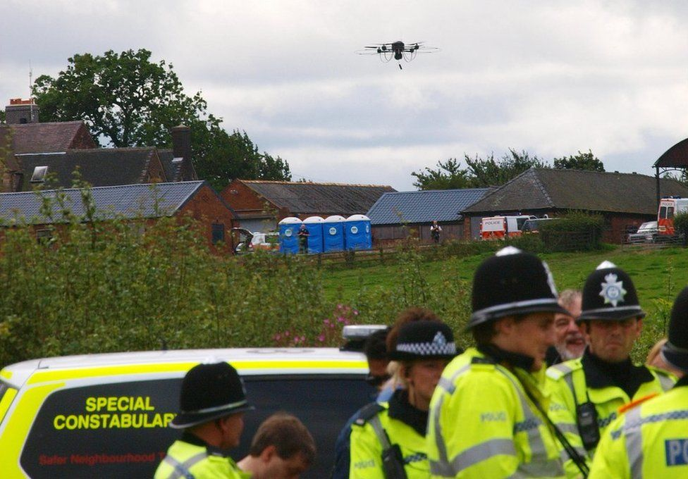 A police drone with cameras flies over a line of police officers blocking anti-BNP protesters near the BNP festival in Codnor on August 15 2009