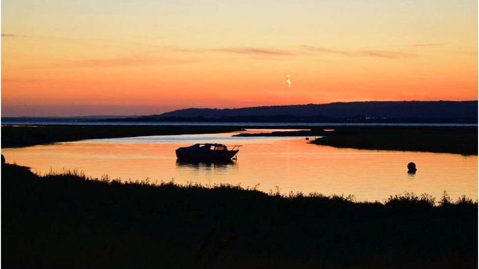 A view of a boat at Penclawdd on Gower at sunset