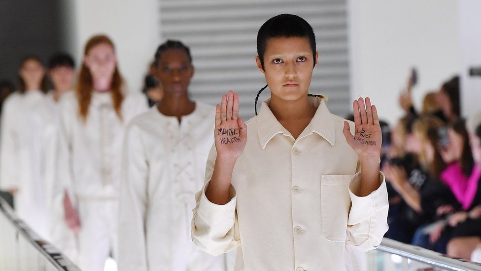 """Ayesha Tan-Jones on the catwalk with """"Mental health is not fashion"""" written on their palms"""