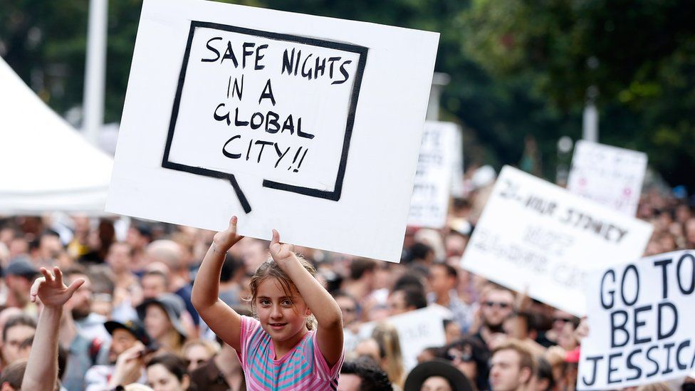 """A protest placard reads: """"Safe Nights In a Global City"""""""