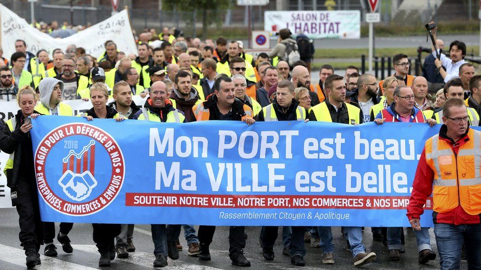 Harbour workers, storekeepers and residents march to participate in a human chain protest demonstration against the migrant situation in Calais