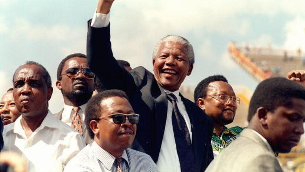 South African National Congress (ANC) President Nelson Mandela gives 15 March 1994 in Mmabatho a clenched fist to supporters upon his arrival for his first election rally for 27 April general elections.