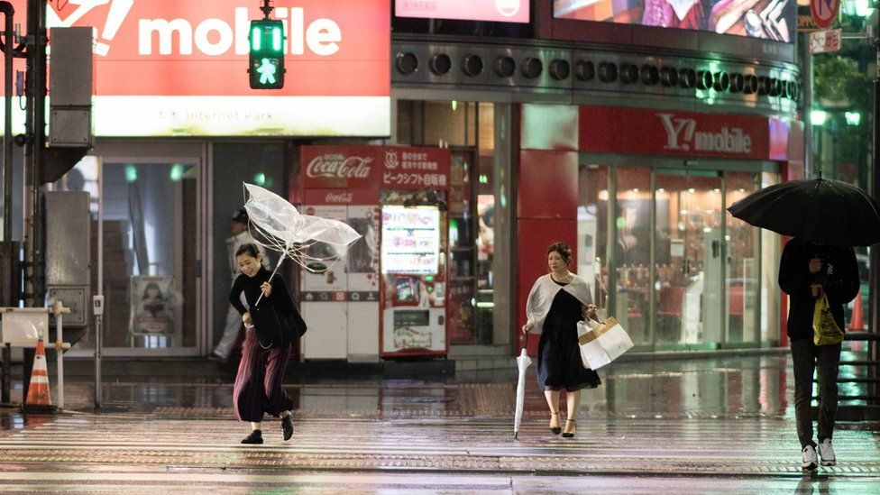 A woman protects herself from the rain with an umbrella in the streets of Tokyo on 30 September 2018