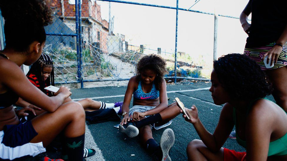 One of the girls, centre, fixes her shoe as the girls talk and check their phones after training