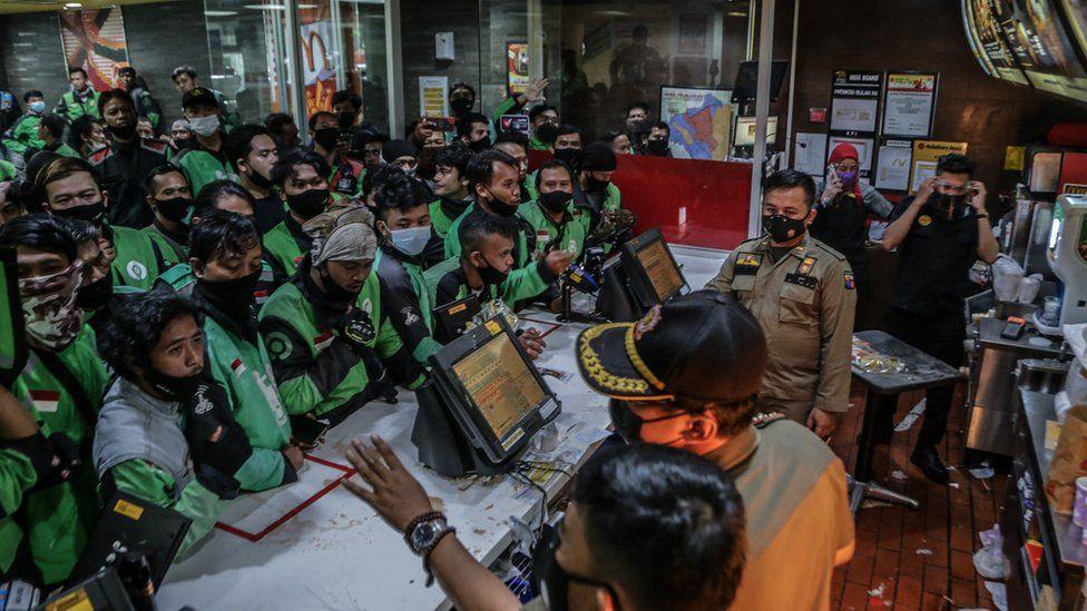 Pengemudi pengiriman makanan mengantri di gerai McDonalds di Bogor pada 9 Juni 2021, untuk membeli paket makanan BTS baru untuk penggemar lapar di negara gila KPop, menyebabkan lebih dari selusin gerai McDonald's tutup sementara karena ketakutan akan virus