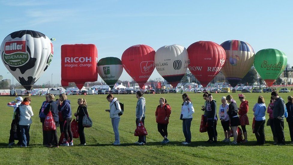 People waiting in a line near air balloons.