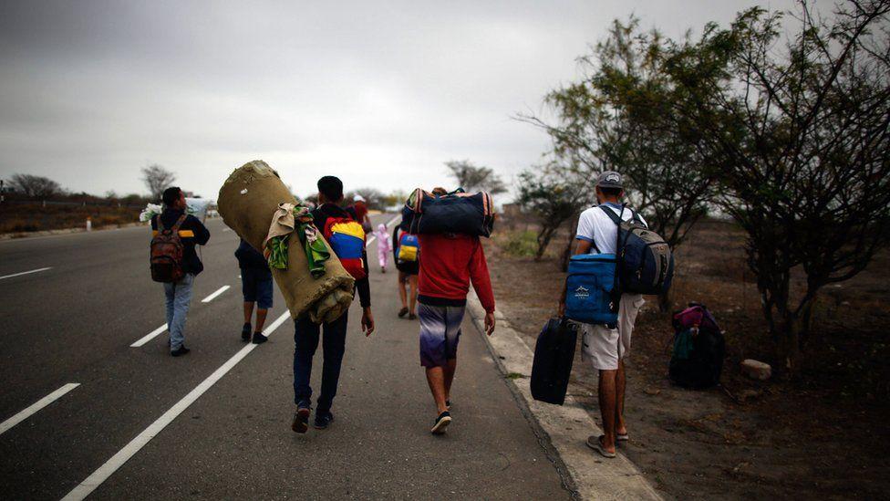 Venezuelan migrants walk alongside a route, after leaving the CEBAF (bi-national border care center) facilities in Tumbes, Peru, near the border with Ecuador, on November 01, 2018.