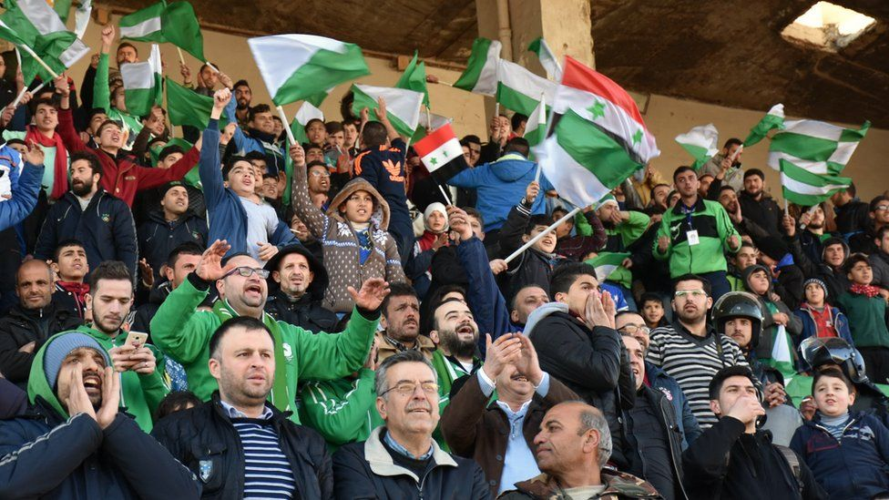 Al-Hurriya supporters wave green and white flags in support of their team from the stands - with one or two Syrian flags interspersed in the crowd