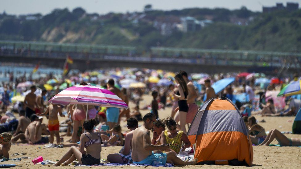 People enjoy the weather on Bournemouth beach in Dorset