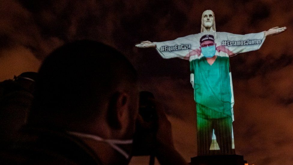 View of the illuminated statue of Christ the Redeemer with an image of a doctor projected onto it