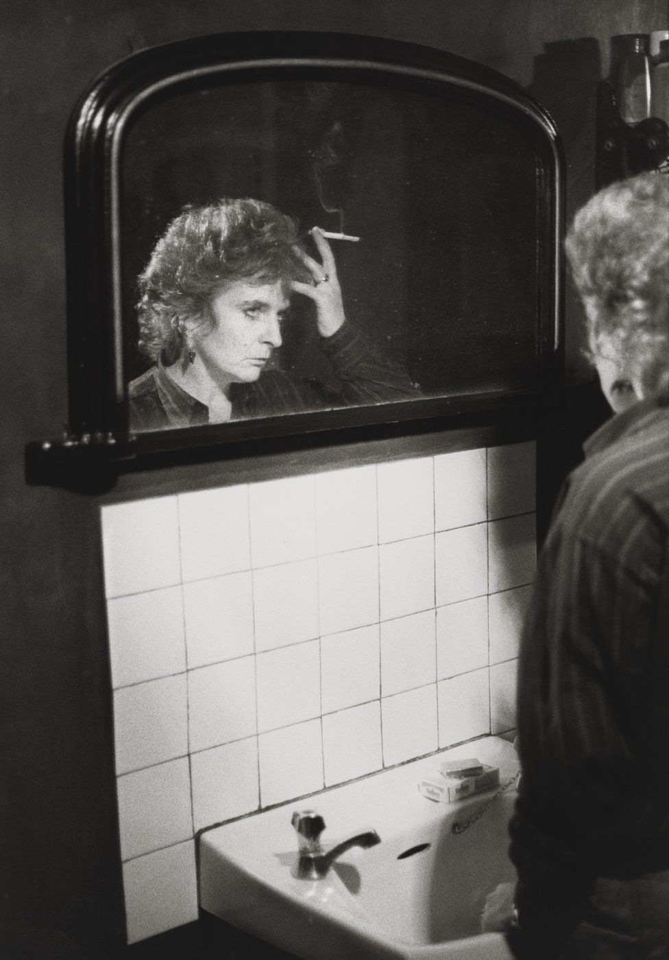 Maggi Hambling stands at the sink, 1984