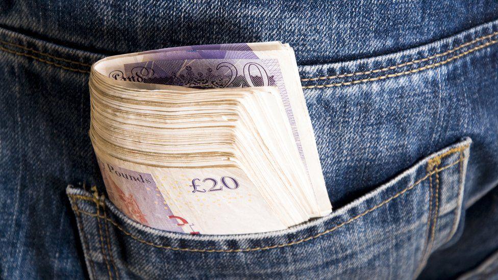 Bundle of cash in a jeans pocket