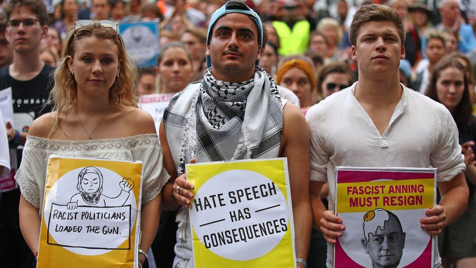 """Protesters hold placards condemning """"racist politicians"""" and """"Fraser Anning"""" in an anti-racism rally in Melbourne"""