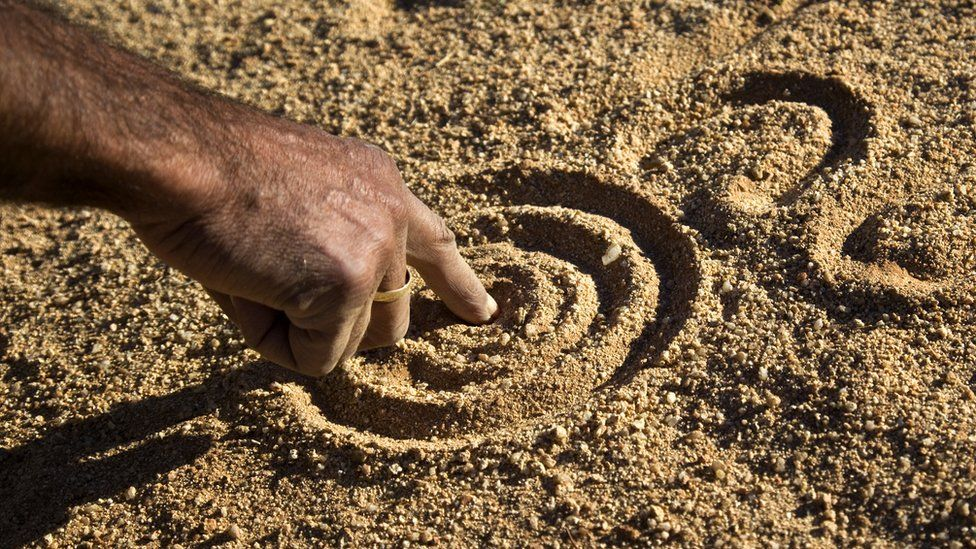 A close up of an Aboriginal man's hand drawing the dreamtime stories in the dirt