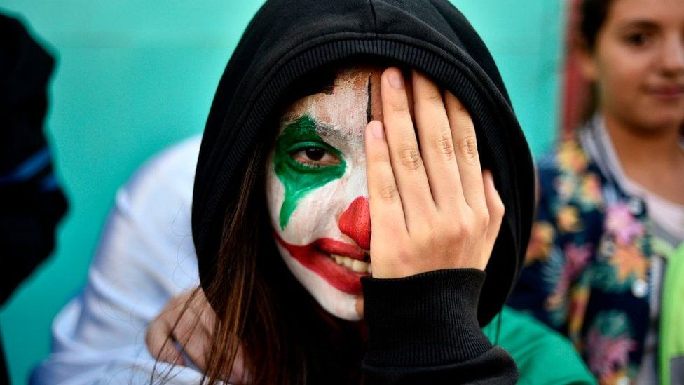 A protester wearing face paint in the colours of the national flag