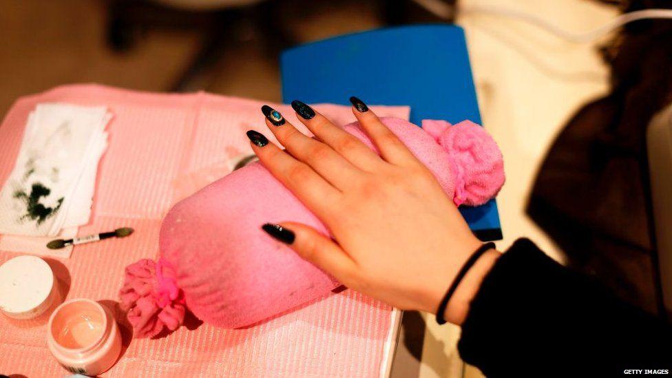 A hand at a nail bar