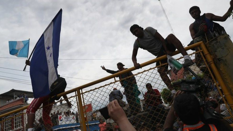 Members of the migrant caravan climb over a gate separating Guatemala from Mexico on 19 October 2018 in Ciudad Tecun Uman, Guatemala.