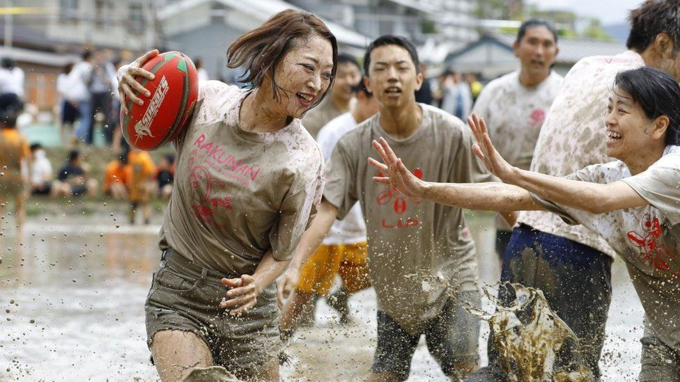 Players slosh through a game of tambo rugby in Kyoto, western Japan
