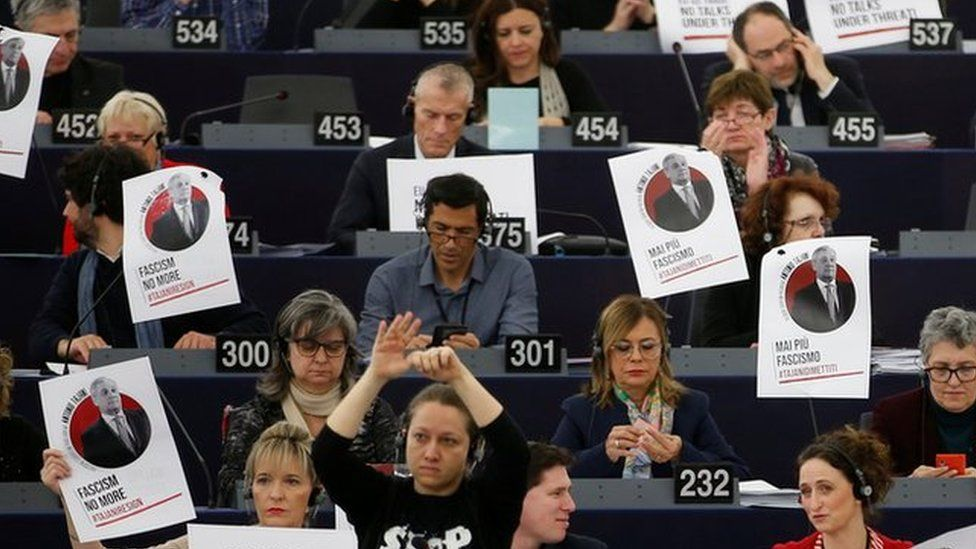"""Portraits of European Parliament President Tajani with the slogan """"never again fascism"""" are placed on the desks of a MEPs during a voting session in Strasbourg"""