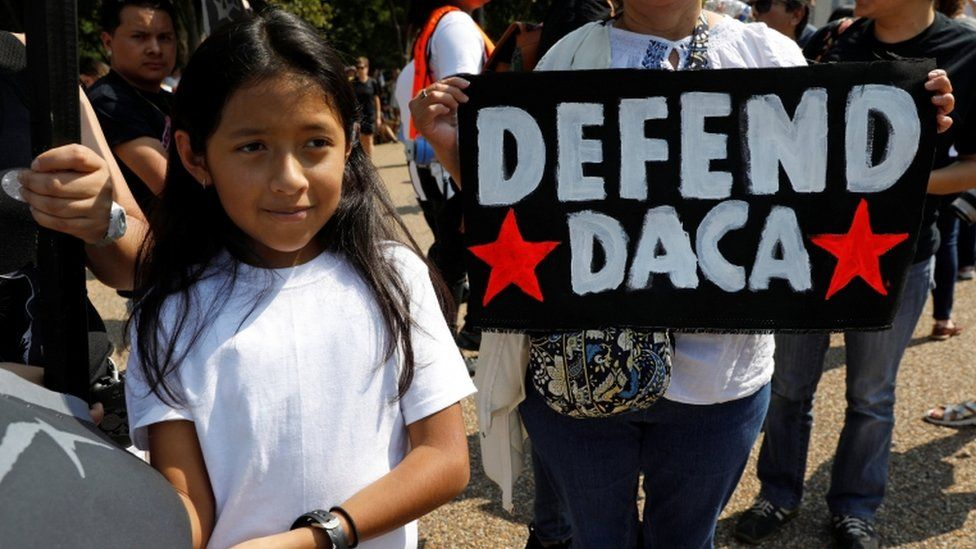 Child stands in front of a 'Defend Daca' sign