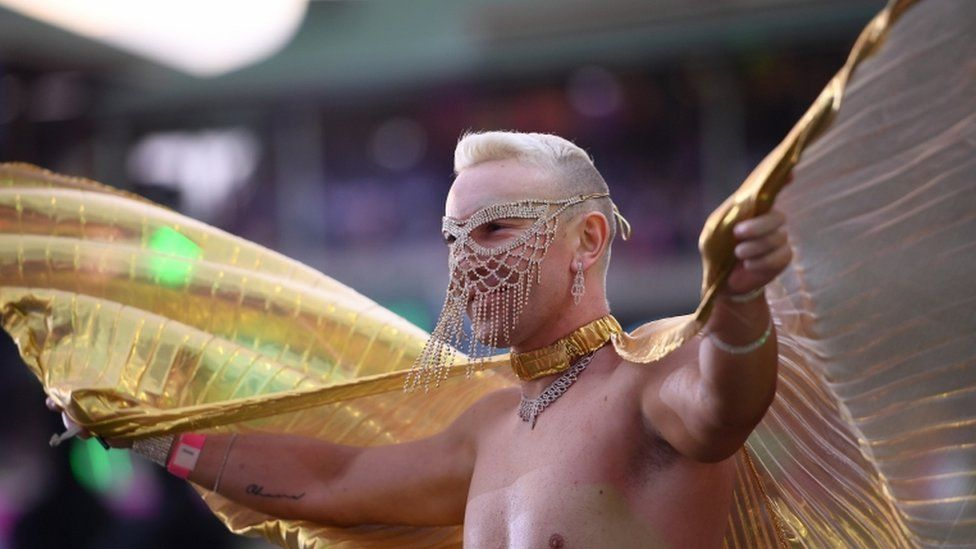 A man wears a jewelled gold face mask and large gold wings during parade